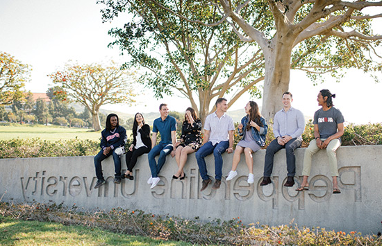 Eight students sitting outside on Pepperdine cement sign