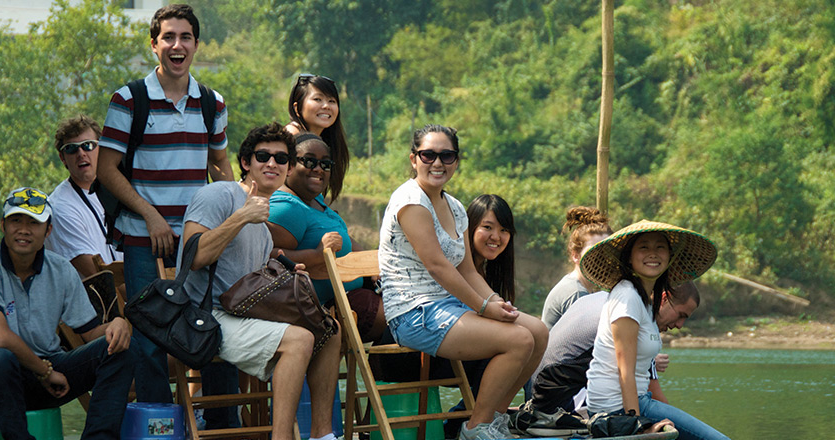 International students sitting on a boat in Shanghai on a river