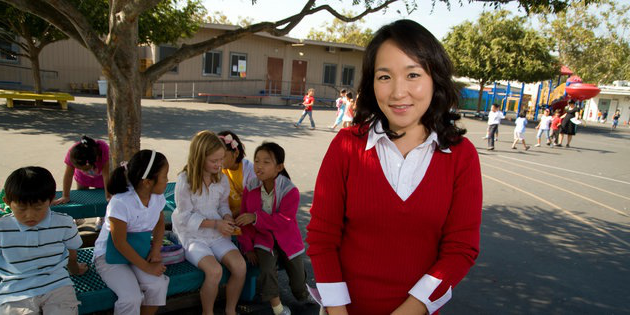 A woman w要么ks with young children at an elementary school - 手机赌博app